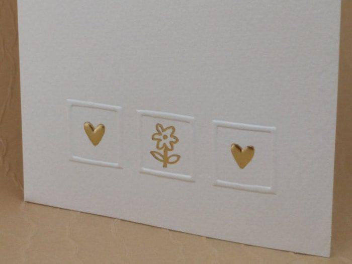 menu cartoncino bianco con cuori e fiore in oro